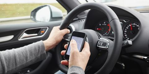 Cropped shot of man using smartphone whilst driving