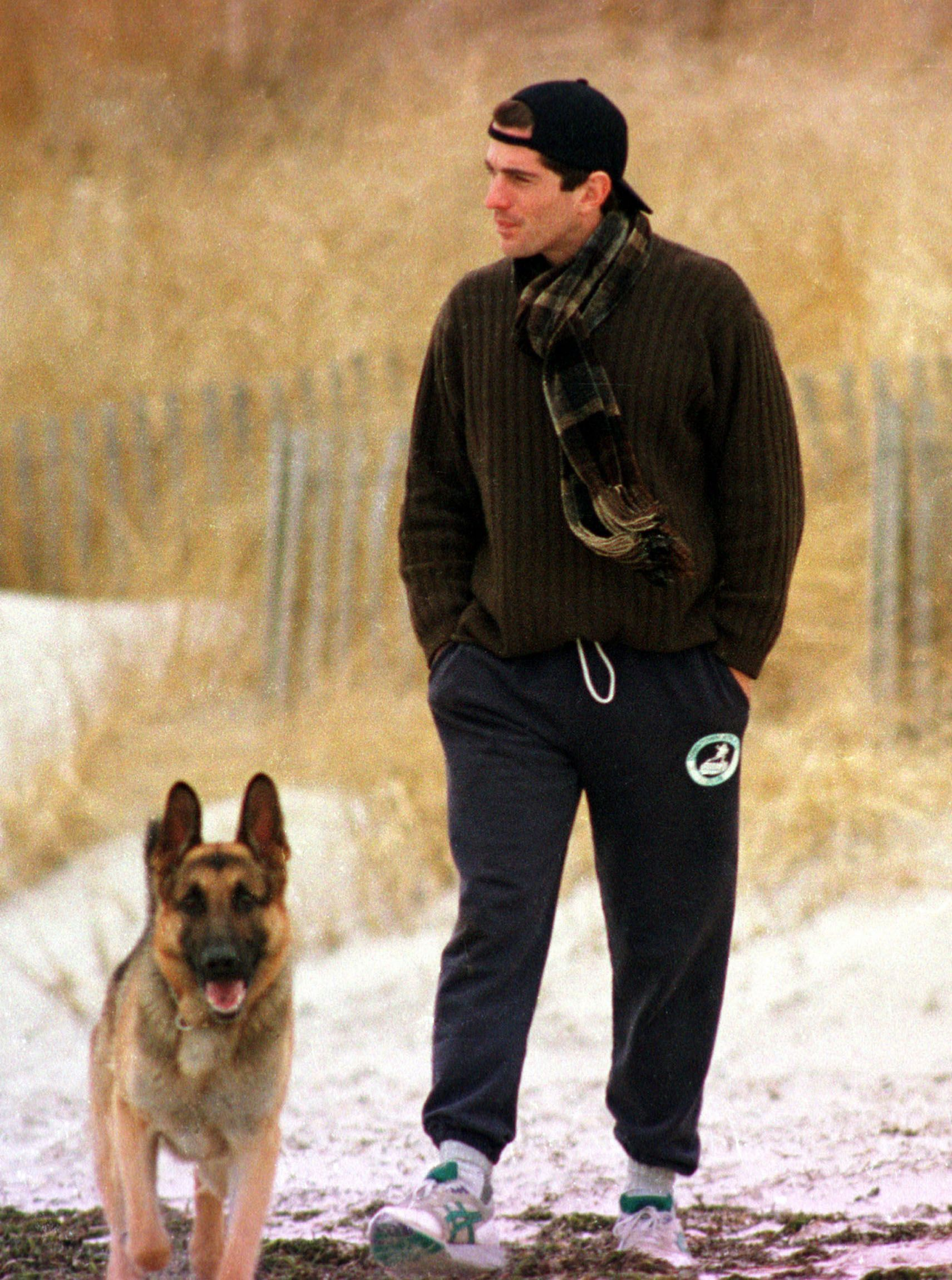 John F. Kennedy Jr. looks out to sea while walking with his dog along the beach in Hyannis Port, Massachusetts, the day after his grandmother Rose Kennedy's death on January 24, 1995.