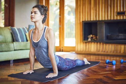 confident young woman saluting to the sun at home fit female is doing stretching exercise on mat she is wearing sportswear