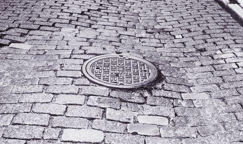 Cobblestone, Manhole cover, Manhole, Brick, Brickwork, Road surface, Black-and-white, Public utility,