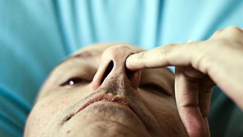 Man peutert in zijn neus.