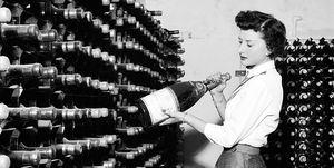 Woman seen here inspecting wine bottles. 1957 A17-001