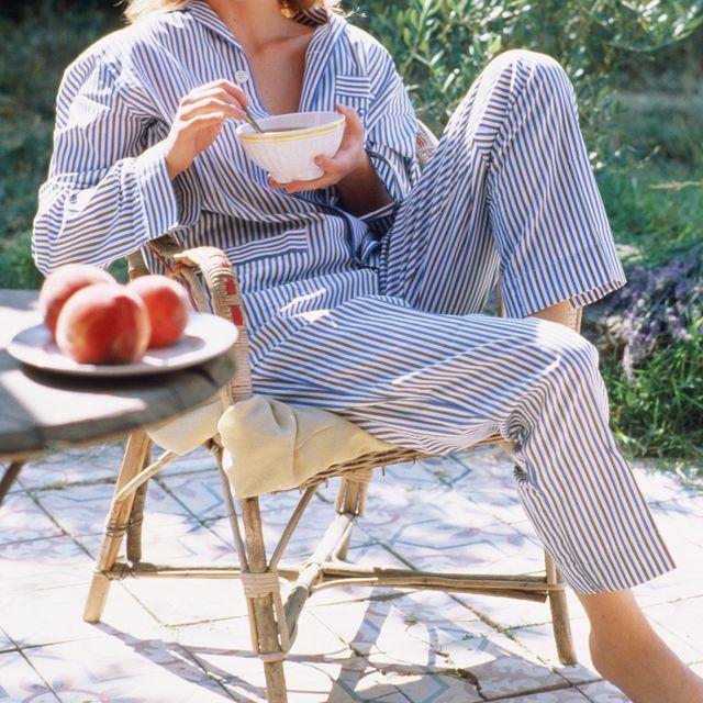 Girl wearing pyjamas having breakfast drink, outdoors
