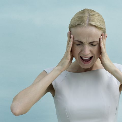 Woman holding head and screaming with eyes closed