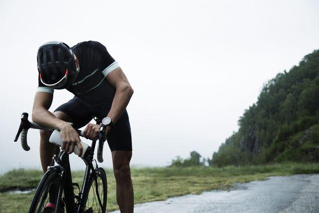 mannelijke wielrenner rust langs de kant van de weg