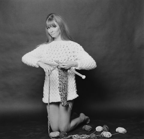 Carol Christopher models a long white knitted sweater called 'Long Island', whilst knitting with maxi-pins (oversize knitting needles), 2nd November 1967