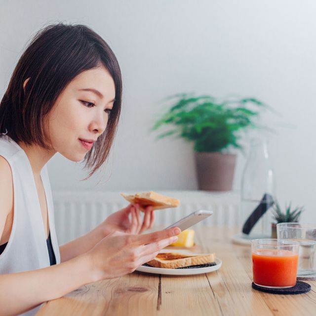 Young lady using smartphone at breakfast
