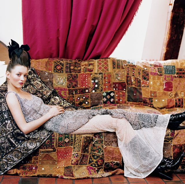 unspecified   march 1  model audrey marnay reclining on a couch covered in a sequin embellished patchwork blanket she is wearing a black and white tulle evening dress reembroidered with a spiral motif encrusted with silver beads, and black patent leather boots, both by atelier versace dress fabric by hurel  credit must read arthur elgortconde nast via getty images photo by arthur elgortconde nast via getty images