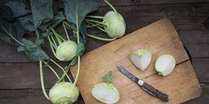 Organic kohlrabi on wood, knife on chopping board, halved