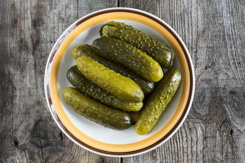 Pickled green gherkins in a bowl on a wooden table