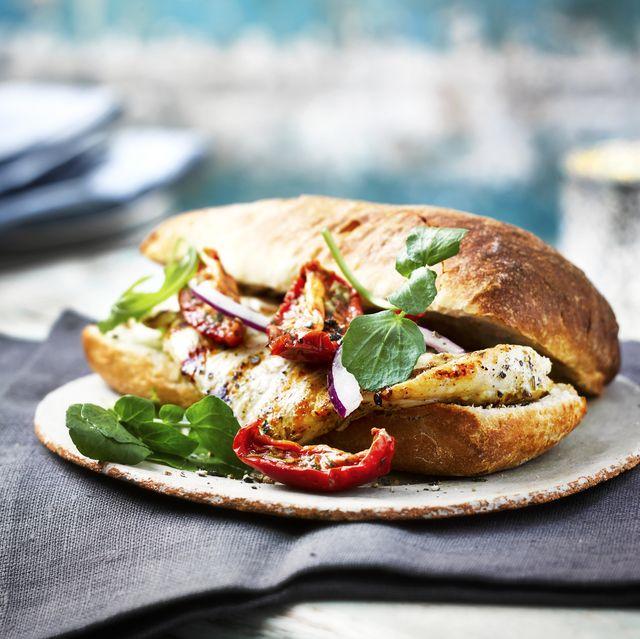 chicken ciabatta ona table with platesa and napkins