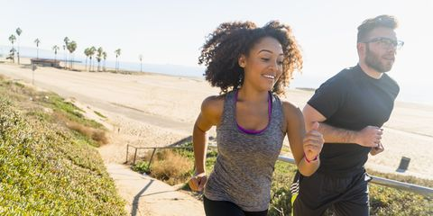 Couple running along pathway by beach