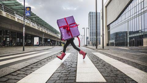 meisje rent met groot cadeau over straat