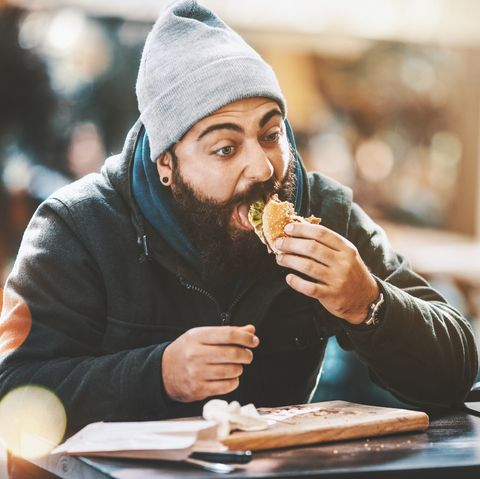closeup of bearded hipster guy gorging on a burger like if nobodys watching hes sitting outdoors on a cold sunny day hes wearing a dark jacket, gray cap and has long brown beard