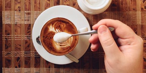 Cropped Hand Holding Sugar Spoon Over Coffee Cup