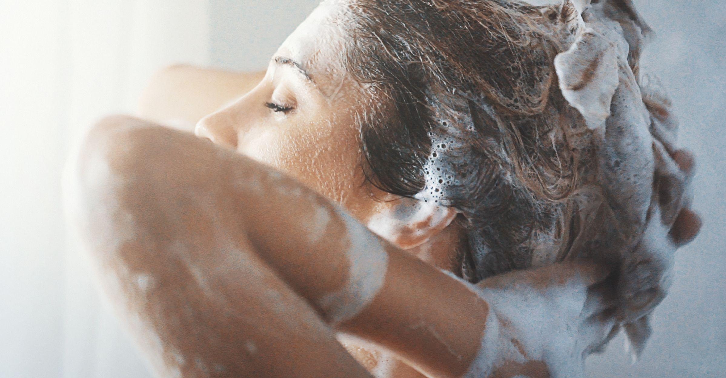 MCU de mujer bajo regadera lavándose cabello