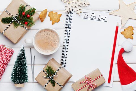 cup of hot cocoa, holiday decorations, gift, present, miniature fir tree and notebook with to do list on white wooden table from above christmas or winter planning concept flat lay style