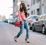 paris, france   november 01  may berthelot fashion and lifestyle blogger maymaryb, is wearing a zara red body with floral print, a zara black lace tank top, maje blue denim boyfriend jeans, louboutin pigalle plato shoes, a golden necklace by 9avril paris, and a chanel red boy bag, on november 1, 2016 in paris, france  photo by edward berthelotgetty images