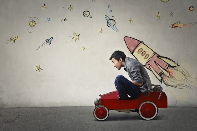 the portrait of a young asian guy in a red toy car in front of a gray wall with spaceship and planets