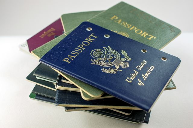 stack of several old and cancelled passports, primarily usa, covid 19 cannot renew passport, passport applications delayed