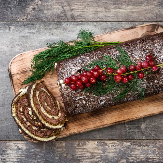 chocolate yule log cake with red currant on wooden background