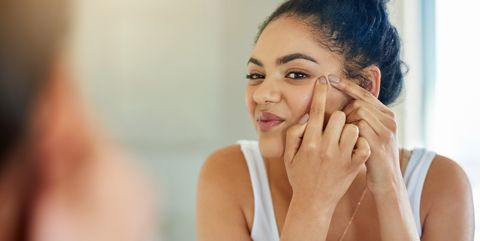 Woman squeezing face in the mirror