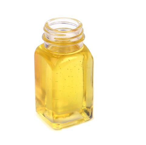 castor oil in glass bottle on white background
