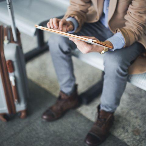Man uses digital tablet in lounge airport