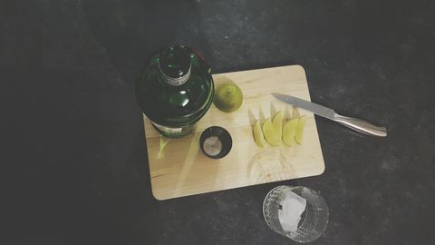High Angle View Of Gin And Tonic With Lemons On Cutting Board