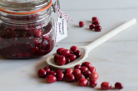 food styling image cranberry sauce in a jar with tag label, cranberries and woods spoon