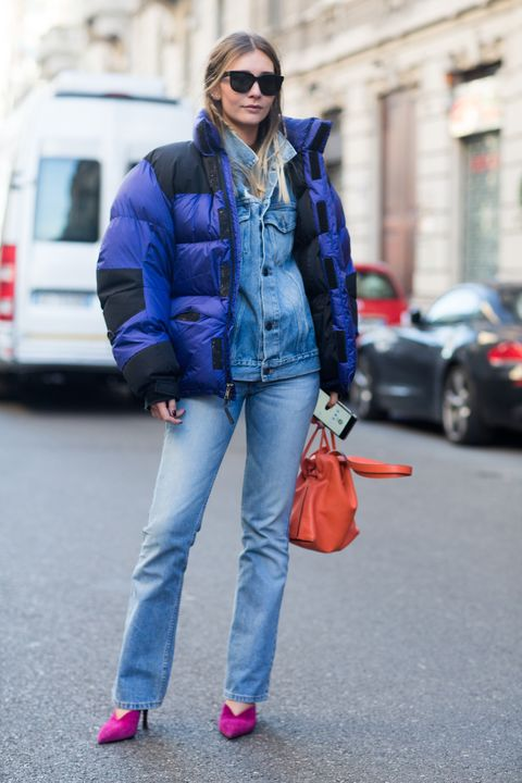 milan, italy   january 15  chiara capitani  wears a blue north face puffer jacket over a denim jacket, flared jeans, an orange loewe bag, and pink kitten heels during milan mens fashion week fallwinter 201718 on january 15, 2017 in milan, italy  photo by melodie jenggetty images