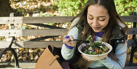 Young woman sitting on park bench eating salad lunch