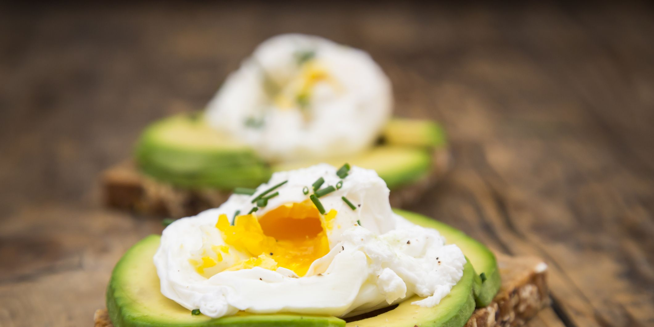 Wholemeal bread slices with sliced avocado and poached eggs on wood