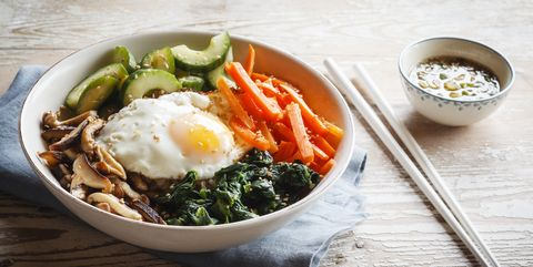 Vegetarian korean rice bowl with mushroom, spinach, cucumber, carrot and fried egg