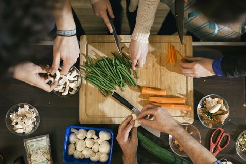 close up of hands cutting vegetables on a wooden board in cooking class food like beans, carrots and mushrooms are getting ready to be cooked on a kitchen desk