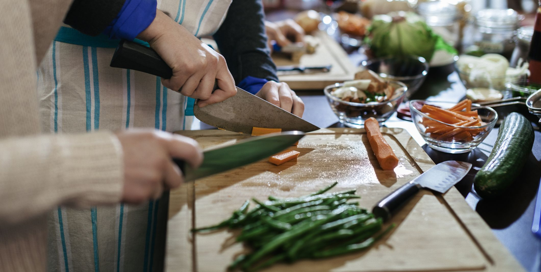 Participants of cooking class cutting carrots
