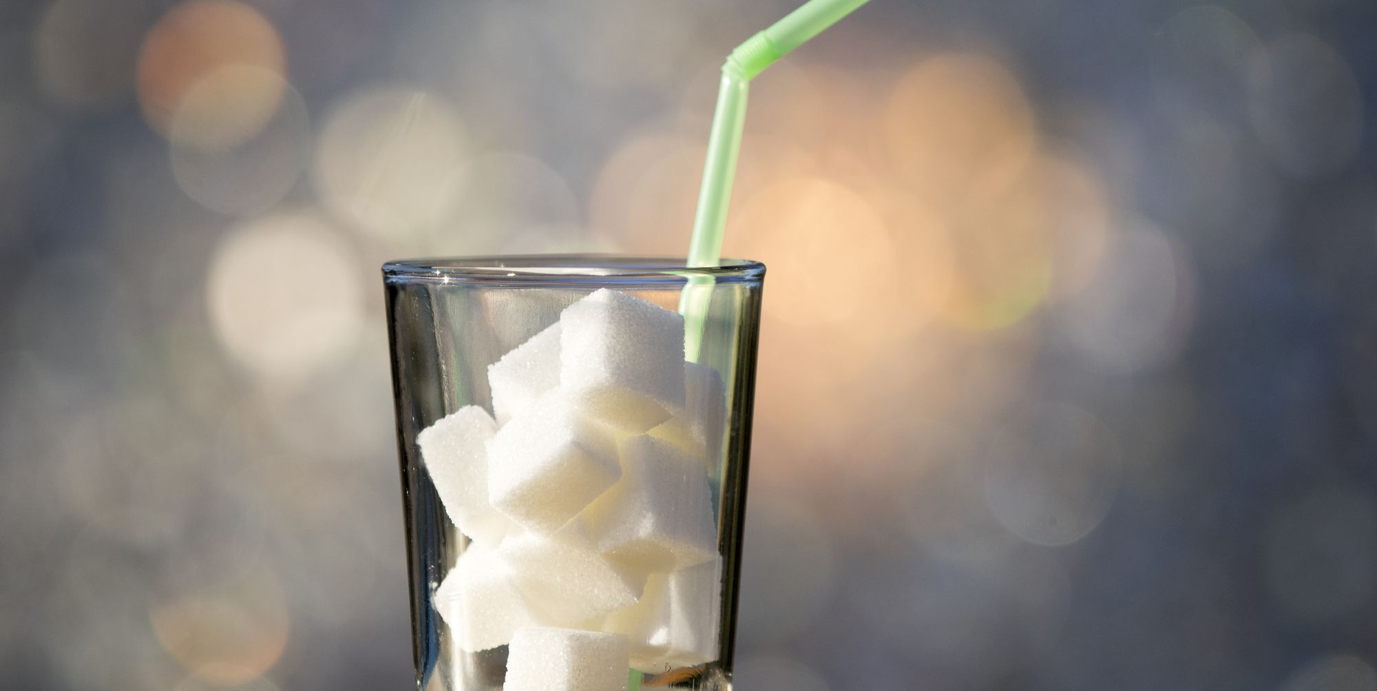 Glass of crystal with a straw  and heap of sugar cubes , it is the equivalent in sugar to a drink of refreshment sweetened
