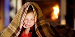 Adorable little girl using tablet by fireplace on Christmas evening