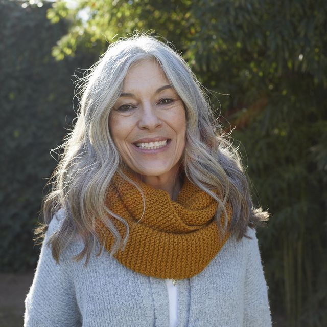 Portrait of woman with long gray hair looking at camera smiling