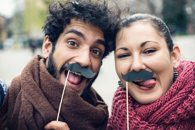couple making funny faces and making selfie with fake moustaches