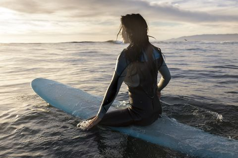 Woman Surfer Sitting on a Surfboard