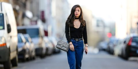 paris, france   february 19  may berthelot, head of legal at videdressingcom and fashion blogger, wears an ivy revel black low neck top, an ivy revel black choker, newlook mom blue denim jeans pants, bash heels, a gucci gg belt, and a chanel tweed timeless white bag, on february 19, 2017 in paris, france  photo by edward berthelotgetty images