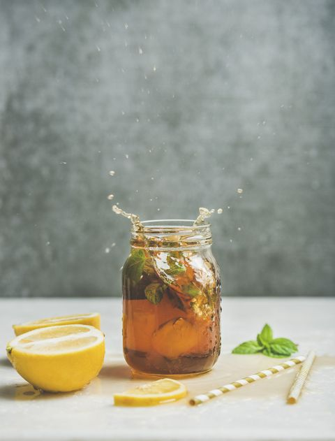 summer cold iced tea with fresh bergamot, mint and lemon in glass jar with splashes on light table, grey concrete wall at background, copy space food in motion concept