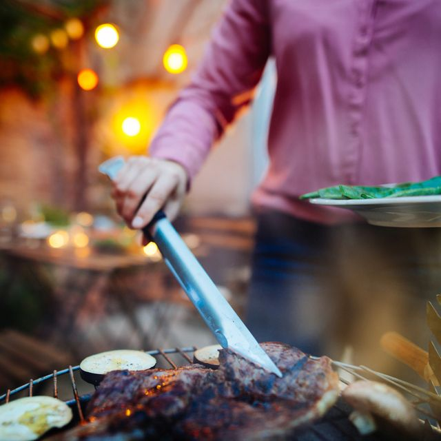 woman barbecuing with open flame grill outdoor