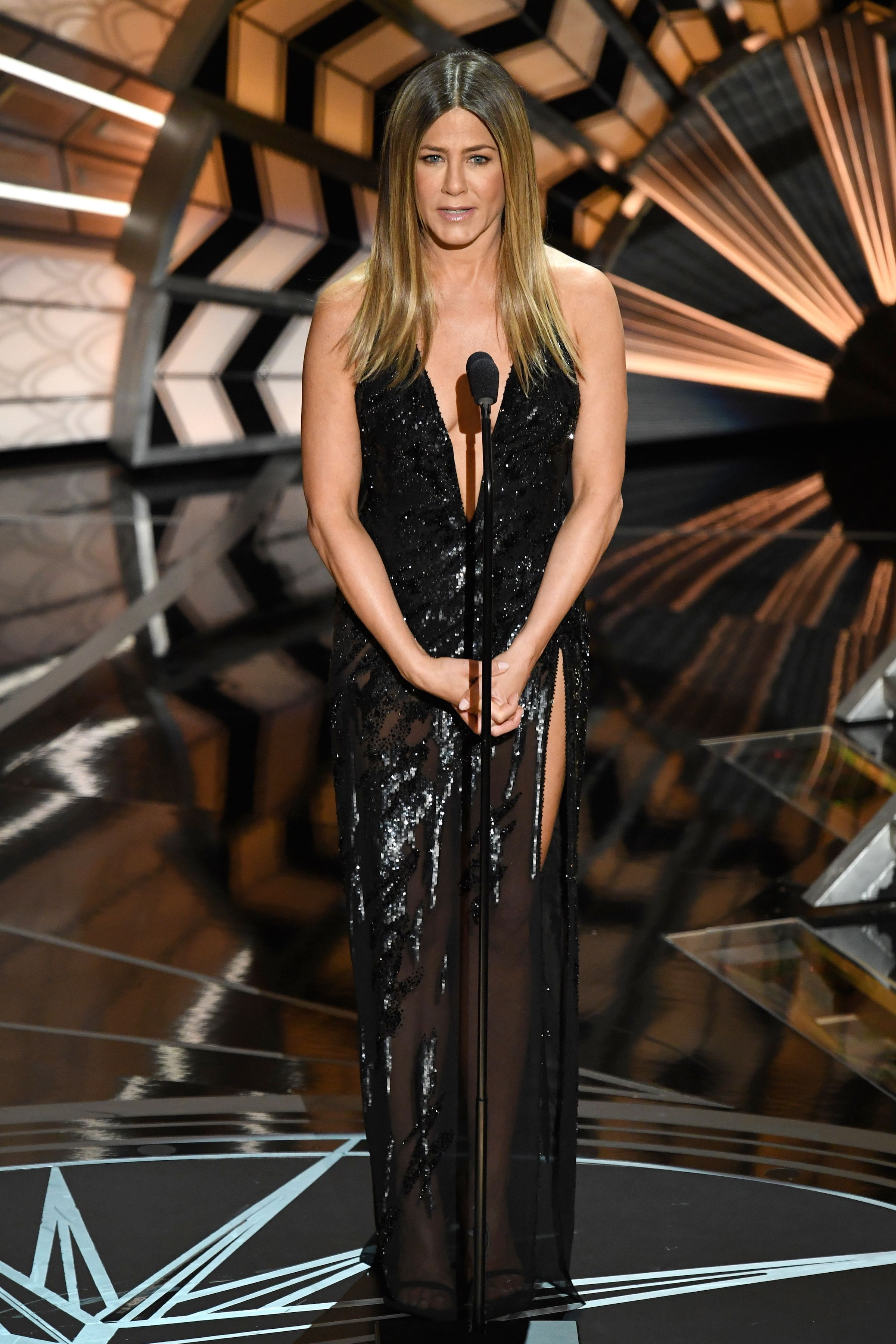 Jennifer Aniston, 2017 Aniston presenting an award in Atelier Versace proves that black doesn't have to mean boring. The open leg, v-neck style has been popular recently among celebrities like Jennifer Lawrence .