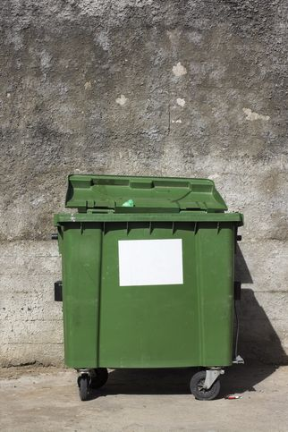 the lonely forgotten green trash bin in captivity of concrete walls