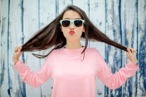 Una chica joven y sonriente juega con su pelo para ilustrar un test sobre cómo prevenir la caída del cabello con productos Phyto