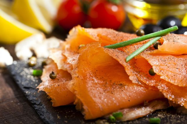 close up view of a slate tray with smoked salmon on rustic wood table dsrl studio photo taken with canon eos 5d mk ii and canon ef 100mm f28l macro is usm