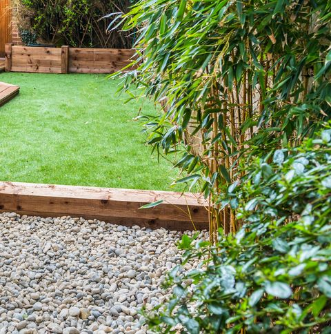 A section of a residntial garden, yard with wooden decking and artificial grass