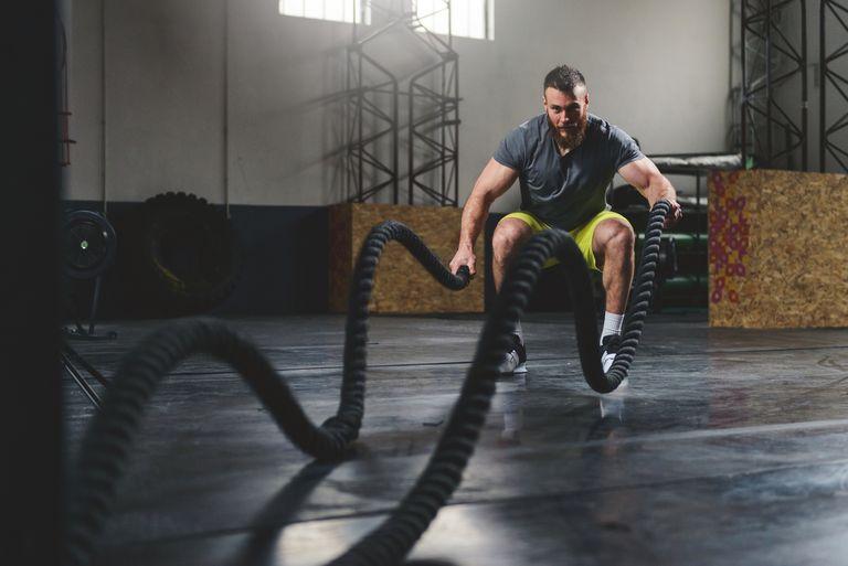Seorang pria latihan kardio menggunakan battling ropes